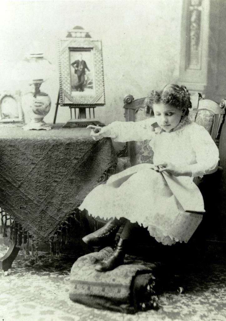 Helen de pequeña, leyendo un libro braille, sentada